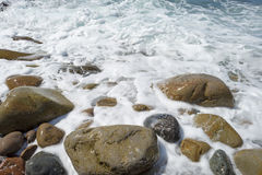 Stones in a foamy sea Stock Photo