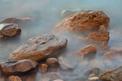 Stones in foggy water Stock Photography