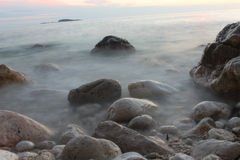 Stones in foggy water. Stones at beach long exposure gives foggy mood to scene Royalty Free Stock Photos