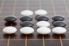 Stones during go game playing on wooden board. Position of stones during go game playing on wooden board close up Stock Photos