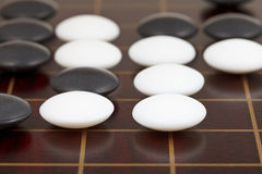 Stones during go game playing on wooden desk Stock Photography