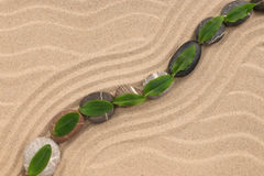 Stones and green leaf on the sand with dunes and waves. Spa and zen concept. View from above Stock Photos