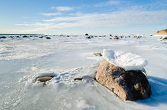 Stones in the ice on the Baltic Sea coast Stock Photos