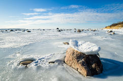Stones in the ice on the Sea coast Stock Photography