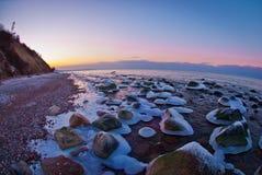 Stones in ice 'skirts' on the seashore. Stock Photos