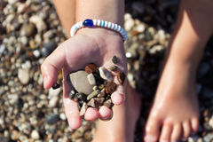Free Stones In The Hand Of The Little Boy Sitting On The Beach Stock Photo - 46424050
