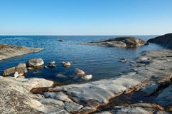 Stones of The Ladoga. Naked stone coast of the Ladoga, the blue sky, blue water Royalty Free Stock Photo