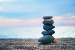 Stones laid out in the form of a pyramid on the seashore. Stones balance and wellness retro spa concept, inspiration, zen-like and well being tranquil Stock Photo