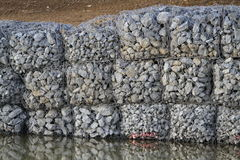 Stones lined with mesh covering beside road, Royalty Free Stock Images
