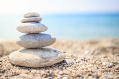 Stones are lined with pyramid on beach. Pebbles. Stones pyramid symbolizing zen, harmony. Balance on ocean background. pebble stack on sea coast line. Stones stock image