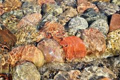 Stones. The stones lying at the bottom of the artificial stream. They give the impression of naturalness. Water flows with the speed and creates a unique game of Stock Images