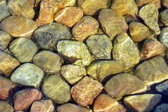 Stones. The stones lying at the bottom of the artificial stream. They give the impression of naturalness. Water flows with the speed and creates a unique game of Stock Photos