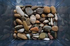 Stones of many types and sizes. Close-up view of pebbles in the box. Top view, marine concept royalty free stock images
