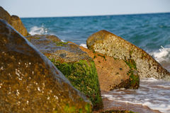 Stones with moss in the surf Royalty Free Stock Photos