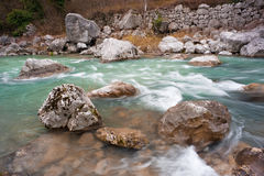 Stones in mountain river. Rapid clear turquoise currents Stock Images