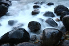 Stones in mountain streams washing. Smooth black stones Royalty Free Stock Image
