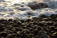 Stones and the ocean on a beach on Tenerife, Canary, Spain, Europe. Stones and the water of the ocean at sunset on the canarian island Tenerife which belongs to royalty free stock images