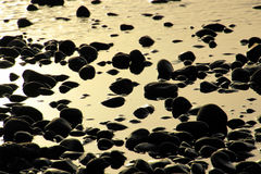 Stones and the ocean on a beach on Tenerife, Canary, Spain, Europe. Stones and the water of the ocean at sunset on the canarian island Tenerife which belongs to Stock Photo
