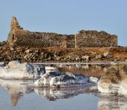 Stones and old construction in salt lagoon Stock Image