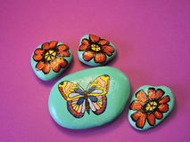 Stones with painted butterfly and flowers Stock Image