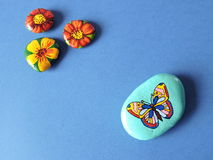 Stones with painted butterfly and flowers Stock Photo