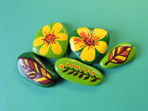 Stones with painted flowers and leafs Stock Images