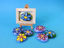 Stones with painted flowers. Natural stones with painted  flowers on blue background Royalty Free Stock Images