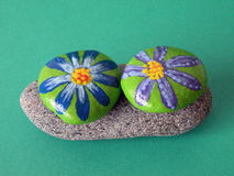 Stones with painted flowers Royalty Free Stock Image