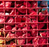 Stones painted with red paint in a metal grid as a background.  royalty free stock photos