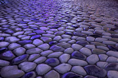 Stones and patterns. Pebbles on the ground under the neon light irradiation Stock Photography