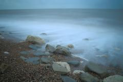 Stones on the pebble beach with blurred sea waves Royalty Free Stock Image