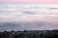 Stones on pebble beach and sea water at sunset. Background. With copy space Stock Photo