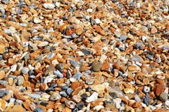 Pebble beach of big oval colorful stones brightly illuminated. royalty free stock image