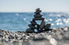 Stones and pebbles stack, harmony and balance, One big pyramid stone cairn on seacoast. Sea reflections Royalty Free Stock Photos