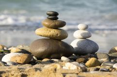 Stones and pebbles stack, harmony and balance. One stone cairn on seacoast, sea waves on background, pebble sand beach, sunlight, wild nature, concept of Royalty Free Stock Photography