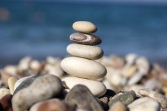 Stones and pebbles stack, harmony and balance, one stone cairn on seacoast. Sunlight, blue background, among group of stones Stock Image