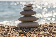 Stones and pebbles stack, harmony and balance, one stone cairn on seacoast. Success emotion, reflections on the water Stock Photo