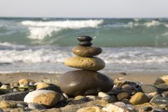Stones and pebbles stack, harmony and balance. One stone cairn on seacoast, sea waves on background, pebble beach, sunlight, wild nature, concept of success Royalty Free Stock Images