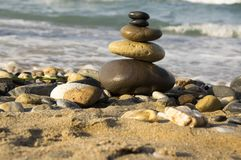 Stones and pebbles stack, harmony and balance. One stone cairn on seacoast, sea waves on background, pebble sand beach, sunlight, wild nature, concept of Royalty Free Stock Image