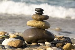 Stones and pebbles stack, harmony and balance. One stone cairn on seacoast, sea waves on background, pebble sand beach, sunlight, wild nature, concept of Stock Image