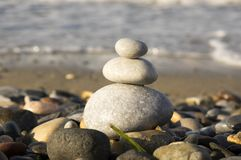Stones and pebbles stack, harmony and balance. One stone cairn on seacoast, sea waves on background, pebble sand beach, sunlight, wild nature, concept of Stock Photos