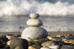 Stones and pebbles stack, harmony and balance. One stone cairn on seacoast, sea waves on background, pebble sand beach, sunlight, wild nature, concept of Stock Images