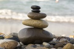 Stones and pebbles stack, harmony and balance. One stone cairn on seacoast, sea waves on background, pebble sand beach, sunlight, wild nature, concept of Stock Photography