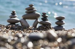 Stones and pebbles stack, harmony and balance, three stone cairns on seacoast with ocean waves. On background, sunlight and reflections Royalty Free Stock Image