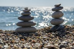 Stones and pebbles stack, harmony and balance, two stone cairns on seacoast. Coastline, sea reflections Stock Photos