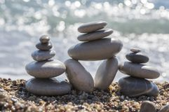 Stones and pebbles stack, pebble cairn. Stones and pebbles stack, harmony and balance, three stone cairns on seacoast with ocean waves on background Royalty Free Stock Images