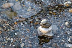 Stones piled up on the shore of a lake with stones in the background stock photos
