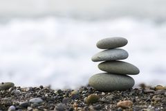 Stones pyramid on Black sea beach symbolizing stability, zen, harmony, balance. Shallow depth of field Stock Photos
