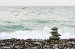 Stones pyramid on Black sea beach symbolizing stability, zen, harmony, balance. Shallow depth of field Royalty Free Stock Image
