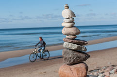 Stones pyramid with cyclist at sea. Stock Image